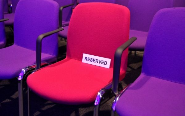 one pink seat with reserved sign in a row of red seats, how to win government contracts successfully